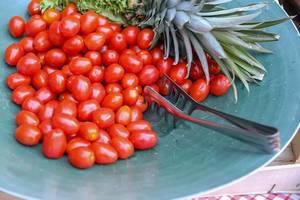 Kleine, reife Tomaten liegen mit einer Salatgabel und neben einer Ananas auf einem türkisen Teller