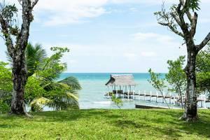 Kleiner Bootssteg mit Palmendach am Meer