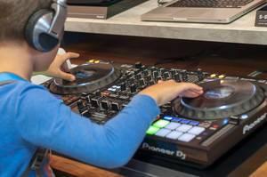Kleiner Junge versucht sich als DJ mit einem DJ Mischer von Pioneer