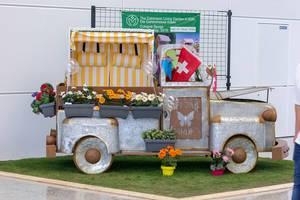 Kleiner Lieferwagen aus Blech mit Blumentöpfen als Garten-Deko