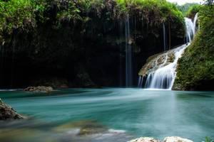 Kleiner Wasserfall führt über mit Moos bewachsenen Felsen in türkisblauen See