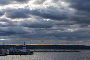 Kleiner weiß-roter Leuchtturm bei bewölkter Abenddämmerung im Hafen von Lahti, neben einem Hausboot, am Vesijärvi-See