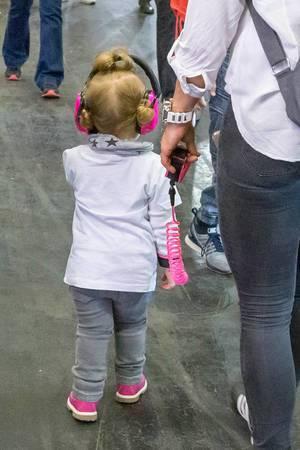 Kleines Mädchen mit pinkem Kopfhörer an Kindleine geführt an der Fibo-Messe Köln