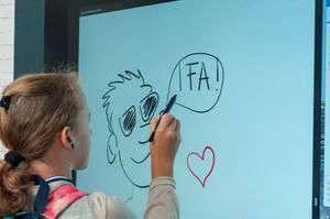 Kleines Mädchen zeichnet mit einem Stylus auf einem große Bildschirm