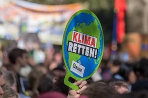 Klima Retten Schild in der Form eines Globus in der Hand eines Demonstranten