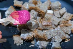 Knalliges Essen: Rote Bete Hummus auf einem Holzlöffel und Brotstücke im Hintergrund