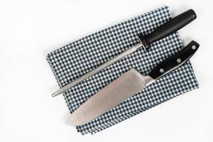 Knife and Knife Sharpener on the kitchen dishcloth on the white background
