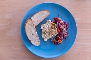 Knoblauch-Fladenbrot und Gebackener Hirtenkäse mit Tomaten-Zwiebel Gemüse auf einem blauen Teller in der Aufsicht