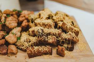 Knoblauch-Käse Toast und gebratenes Hunch Snacks auf einem Holztisch