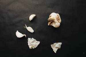 Knoblauchknolle und verstreute Knoblauchzehen vor dunklem Hintergrund. Draufsicht