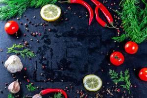 Knoblauchzitondill und -gewürze mit Kirschtomaten auf einem dunklen Hintergrund