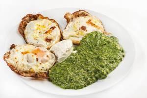 Knusprig angebratene pochierte Eier mit Rahmspinat und Crème fraîche auf weißem Teller