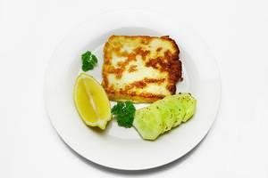 Knusprig braun gebackener Halloumi Käse mit Gurkenscheiben, Zitrone und Petersilie auf Teller