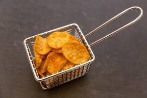 Knusprige Kartoffelchips von IronMaxx als gesunder Snack für Sportler mit Paprikagewürz und viel Eiweiß,  in einem kleinen Fritierkorb