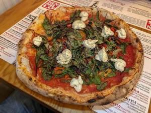 Knusprige Pizza in Pizzeria mit frischem Basilikum und nicht geschmolzenem Mozzarella Käse