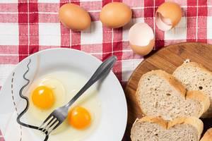 Kochen von French Toast mit Brotscheiben und aufgeschlagenem Ei neben Eiern und Eierschale