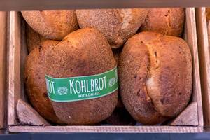 Kohlbrot mit Kümmel: mehrere Brotlaibe in einer alten Holzkiste, aus der Sicht von oben