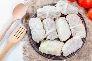 Kohlrouladen mit Reis- und Fleischfüllung, auf einem Leinentuch mit Küchenutensilien
