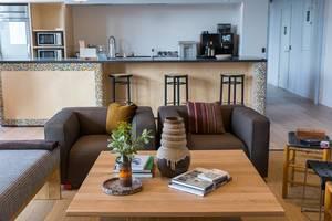 Kölner WeWork-Aufenthaltsraum mit Sitzmöglichkeiten im Wohnzimmer mit Sesseln und Gemeinschaftsküche mit Barhocker