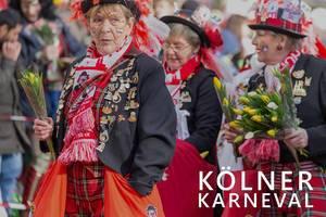 "Kölsch Madel in bunten Kostümen, verteilen Tulpen während des Rosenmontagsumzugs, neben dem Bildtitel ""Kölner Karneval"""