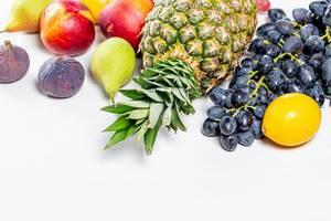 Konzept der gesunden Ernährung: Trauben, Äpfel, Birnen, Ananas, Nektarinen, Zitronen und Feigen auf einem Tisch