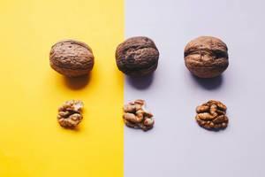 Konzept Food-Fotografie: Walnussschalen und Walnussinneres auf zweifarbiger Unterlage - Nahaufnahme in Draufsicht