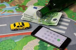 Konzept - Taxidienstleistungen - Ein gelbes Model-Taxi mit Geld, einem Smartphone und einer flasche Bier