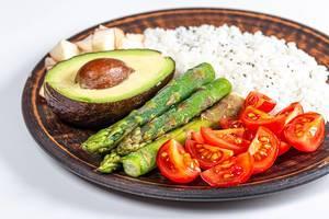 Konzept von gesundem Essen: Tomatenstücke, grüner Spargel, eine halbe Avocado, Äpfelstücke und gekochter Reis