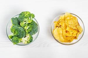 Konzept von gesundem und ungesundem Essen im Vergleich: Schüsseln mit Brokkoli und Chips gefüllt
