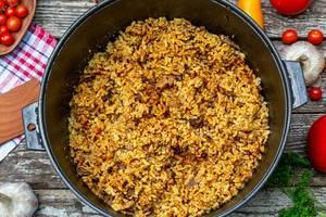 Konzeptbild orientalische Küche: Hausgemachtes Pilaw - serviert im Gusseisen-Kochgeschirr