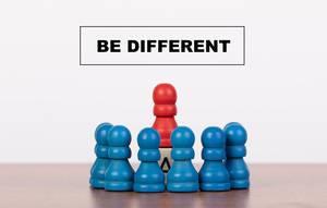 """Konzeptbild """"Anders sein / sich unterscheiden"""", symbolisch dargestellt mit Bauernfiguren auf einem Tisch"""