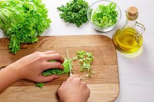 """Konzeptbild """"Gesundes Kochen"""": Frauenhand schneidet Salatblätter auf einem Holzbrett, neben einer Ölkaraffe"""