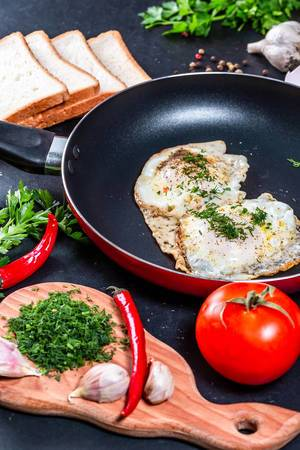 Konzeptbild thematisiert Kochen und Frühstückszubereitung mit Spiegeleier und Kräutern, in der Pfanne, neben Weißbrotscheiben & Gemüse