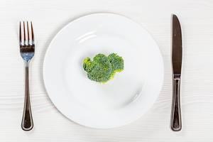 Konzeptbild von gesundem, pflanzlichen Essen: Ein Stück frischer Brokkoli auf einem runden Teller, neben Messer und Gabel