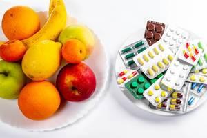 Konzeptbild zeigt Wahl zwischen gesunder Ernährung und Medikamenten-Behandlung, dargestellt mit Tabletten & frischen Früchte