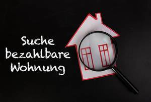 """Konzeptbild zum Thema Gentrifizierung mit dem Text """"Suche bezahlbare Wohnungen""""  mit selbstgebasteltem Papier-Haus unter einer Lupe"""