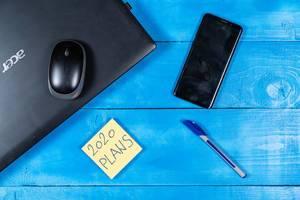 Konzeptbild zum Thema Geschäftsplan für 2020: Notizzettel, Stift, Laptop und Handy auf einem blauen Tisch