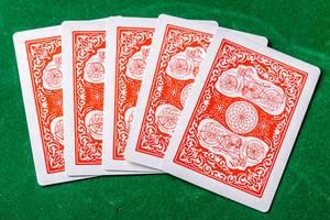 Konzeptbild zum Thema Glücksspiel zeigt fünf verdeckte Spielkarten, vor dem Start des Spiels, auf einer grünen Oberfläche