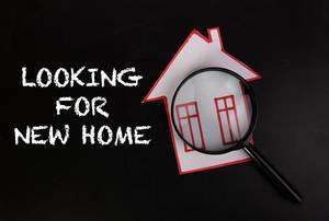 """Konzeptbild zum Thema Haussuche und dem Text """"Looking for New Home"""" - Suche nach einem neuen Zuhause - mit gebastelten Haus unter einer Lupe"""