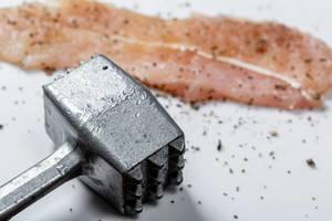 Konzeptbild zum Thema Kochen, mit einem eisernen Fleischhammer, vor einem mit Pfeffer gewürzten, rohen Stück Fleisch