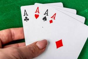 Konzeptbild zum Thema Poker spielen, mit vier Asse in einer Frauenhand, vor einem grünen Pokertisch