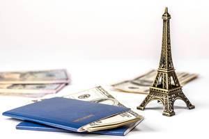 Konzeptbild zum Thema Reiseziel & Freizeitgestaltung zeigt den Eiffelturm neben zwei Reisepässen mit amerikanischen Geldscheinen