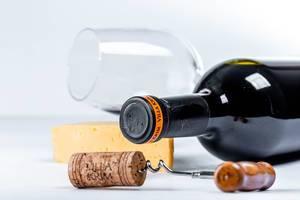 Korkenzieher mit Korken vor einer Weinflasche, Käse und einem Glas, mit weißem Hintergrund