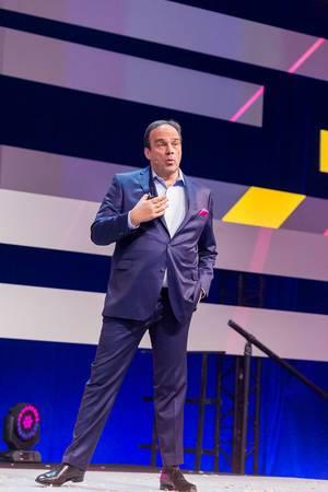 Körpersprache: Hagen Rickmann, der den Geschäftskundenbereich der Deutsche Telekom leitet, hält einen Impulsvortrag mit einer Hand in der Hosentasche seines blauen Anzugs