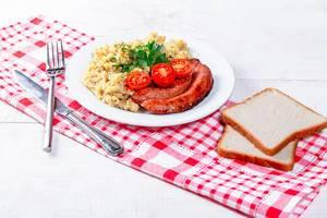 Köstlicher Brei mit Würsten und Brot mit Geschirrtuch auf weißem hölzernem Hintergrund