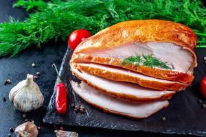 Köstliches Schneiden der geräucherten Hühnerleiste mit Gewürzen auf einem dunklen Hintergrund