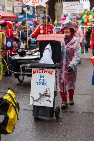 Kostümierte Frau der Pappnasen-Rotschwarz mit Miethai in einer Mülltonne beim Rosenmontagszug in Köln