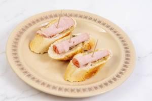 Kräuter Baguettes mit Schinkenscheiben auf einem Teller