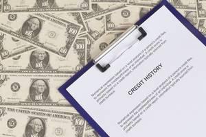 Kredithistorie auf einem Klemmbrett mit Dollar Geldscheinen als Hintergrund