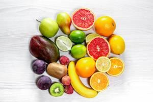 Kreis von frischen Früchten und Obst auf einem weißen Holztisch